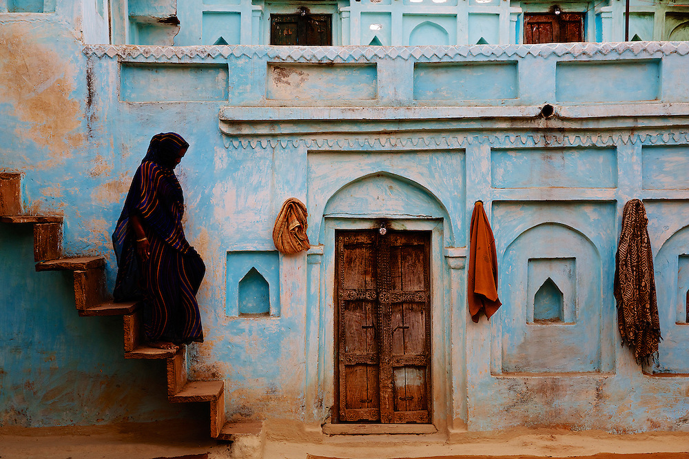 A woman descends the steps wearing a traditional Indian saari, in Bundelkand, India.