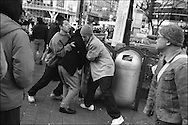 Young men hold another male who they have been scuffling with until police arrive, outside the Shibuya train station, Tokyo, Japan.