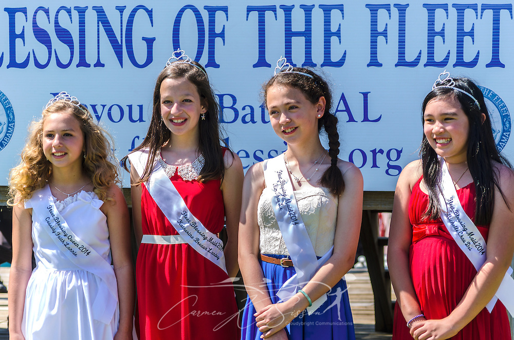 Members of the 65th annual Blessing of the Fleet court wait for Archbishop Thomas J. Rodi (not pictured) to deliver the prayer in Bayou La Batre, Alabama, May 4, 2014. From left are Fleet Blessing Queen Cassidy Faith Lannie and Fleet Blessing maids Katherine Landry, Kim Thao Le, and Michelle Dai. The first fleet blessing was held by St. Margaret's Catholic Church in 1949, carrying on a long European tradition of asking God's favor for a bountiful seafood harvest and protection from the perils of the sea. The highlight of the event is a blessing of the boats by the local Catholic archbishop and the tossing of a ceremonial wreath in memory of those who have lost their lives at sea. The event also includes a land parade and a parade of decorated boats that slowly cruise through the bayou. (Photo by Carmen K. Sisson/Cloudybright)