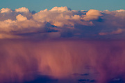 Above the painted desert in Arizona, sheets of heavy rain glow pink at sunset beneath the white clouds of an approaching storm.  The Painted Desert encompasses over 93,500 acres, stretching for over 160 miles, and derives its name for the multitude of colors ranging from lavenders to shades of gray with vibrant reds, oranges and pink.  The area is a long expanse of badland hills and buttes which, although barren and austere, encompass a rainbow of colors due to the colorful sediments of bentonite clay and sandstone. <br /> <br /> The desert is composed of stratified layers of easily erodible siltstone, mudstone, and shale of the Triassic Chinle Formation. These fine-grained rock layers contain abundant iron and manganese compounds which provide the pigments for the various colors of the region.<br /> <br /> The Painted Desert was named by an expedition under Francisco V&aacute;zquez de Coronado on his 1540 quest to find the Seven Cities of Cibola, which he located some forty miles east of here. Discovering that the cities were not made of gold, Coronado sent an expedition to find the Colorado River for supplies. The group passed through the colorful landscape and named the area &quot;El Desierto Pintado&quot; - The Painted Desert.