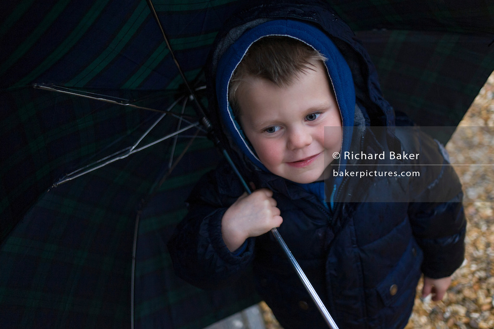 A 4 year-old boy holds an umbrella outdoors in family woods.