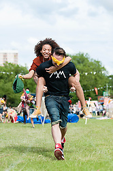 © Licensed to London News Pictures. 08/06/2014. London, UK.  Festival atmosphere at Field Day Festival 2014 - festival goers compete each other in a piggy back race. Field Day is an annual outdoor music festival which takes place in Victoria Park in London.    Photo credit : Richard Isaac/LNP
