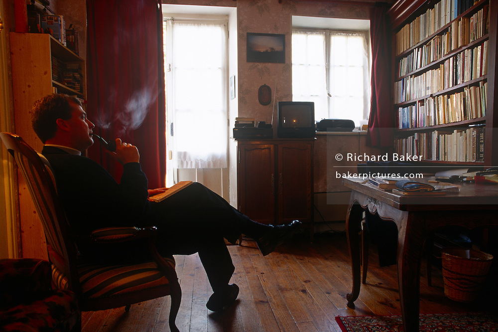 In his private rooms, a priest blows smoke from his pipe in a local Catholic church in rural Normandy.