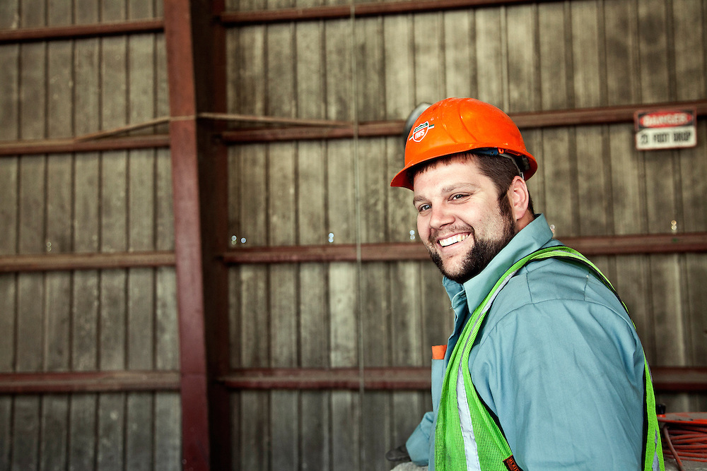 Smiling worker at solid waste transfer station wearing yellow safety vest