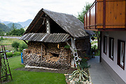 An elaborate stack of logs piles around a barn structure in a Slovenian village, on 18th June 2018, in Bohinjska Bela, Bled, Slovenia.