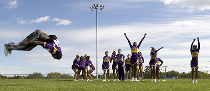 Cheerleaders cheer as the varsity football team is introduced at a pep rally in Rochester, New York.