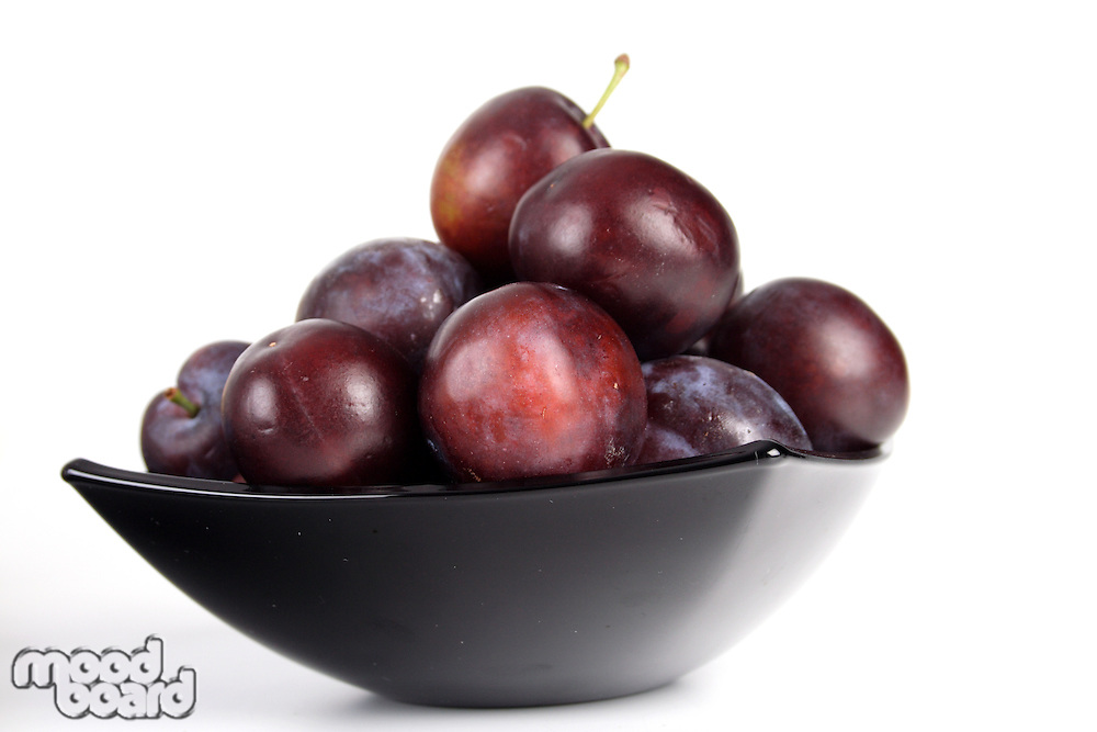 Plums in black bowl - close up