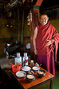 The head monk at his partially rebuilt monastery with his typical day's worth of food in the Tibetan Plateau. (From the book What I Eat: Around the World in 80 Diets.) The caloric value of his day's worth of food in June was 4,900 kcals. He is 45 years of age; 5 feet, 5 inches tall; and 158 pounds.