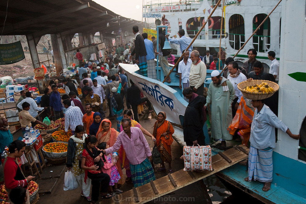 Travelers disembark from a ferry at the Sadarghat dock on the Buriganga River in Dhaka, Bangladesh. The river acts as both a highway and a sewer, with 80 percent of the city's raw sewage draining into it from different parts of the city.
