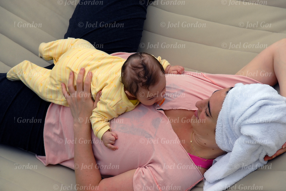 Parent child, infant and mother eye contact, infant lieing on top of mother who is in a hammock