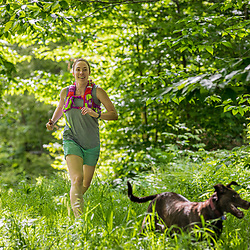 A woman and her dog running in the new Bethel Community Forest in Bethel, Maine.
