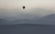 A hot air balloon flies through the valley near Truckee with the Sierra mountains in the background as smoke from the Plumas fire lingers in the early morning air.