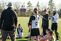 Asst Coach Chuck Buhrman (back to camera) and Coach Beth Doda talk to their team during half time at Interlakes Moultonboro NHIAA DIvision III lacrosse with Belmont on Tuesday afternoon.  (Karen Bobotas/for the Laconia Daily Sun)