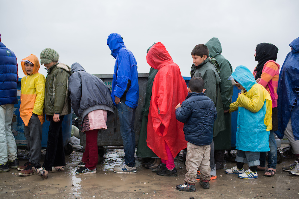 Women and children queuing under the rain for breakfast provided by MSF - Doctors Without Borders at the transit camp of Idomeni, Greece. <br /> <br /> Thousands of refugees are stranded in Idomeni unable to cross the border. The facilities are stretched to the limit and the conditions are appalling.