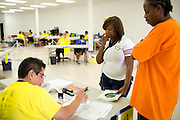 Gabrielle Davis, 16, waits to get her shots with Josh Bacy (left) while Pedro Victoria finishes her paperwork at the Immunization Collaboration of Tarrant County in Fort Worth, Texas on August 30, 2013. The Immunization Collaboration offers low cost vaccines targeting hepatitis, the flu, chickenpox, measles, mumps and HPV amongst other illnesses. (Cooper Neill / for The Texas Tribune)