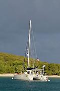 Using a dinghy to access a catamaran sailboat moored in Saltpond Bay, Virgin Islands National Park, St. John, U.S. Virgin Islands.