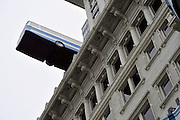 HONG KONG - MARCH 12:  Royal Academy of Arts artist Richard Wilson's work 'Hang On A Minute Lads… I've Got A Great Idea' features a full-sized replica coach that appears to be teetering on the edge of The Peninsula hotel on March 12, 2015 in Hong Kong, Hong Kong.  (Photo by Lucas Schifres/Getty Images)
