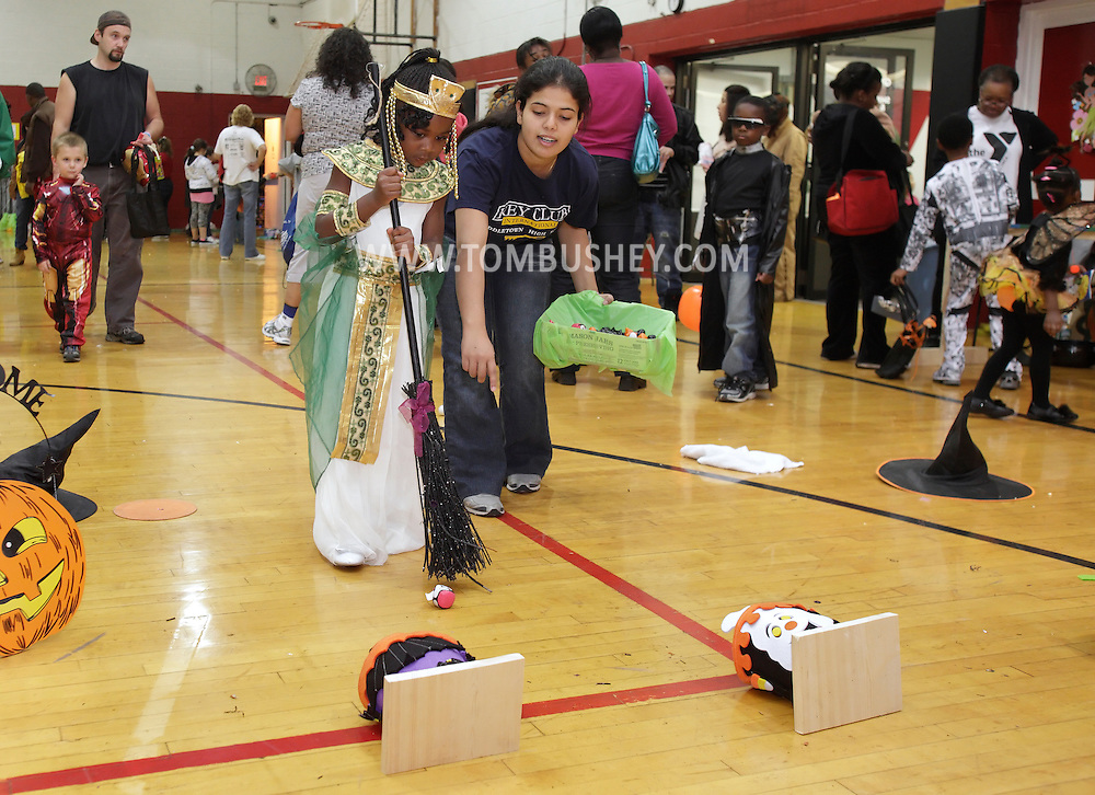 Middletown, New York - A volunteer helps a girl wearing a costume play a game at the Family Fall Festival at the Middletown YMCA on Oct. 23, 2010.