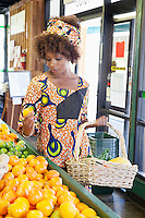 African American woman in traditional wear shopping for fruits at supermarket