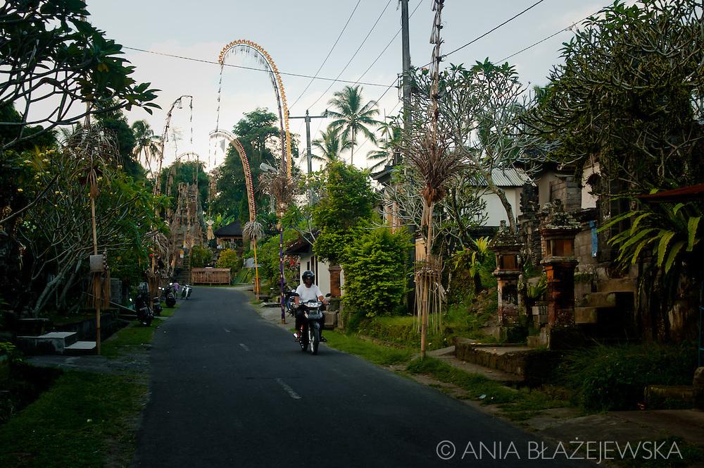 Indonesia, Bali. A tiny traditional balinese village near Ubud. Man riding a motorbike on the street.