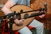 Young Caucasian musician plays an Oud a short-neck lute-type, pear-shaped stringed instrument