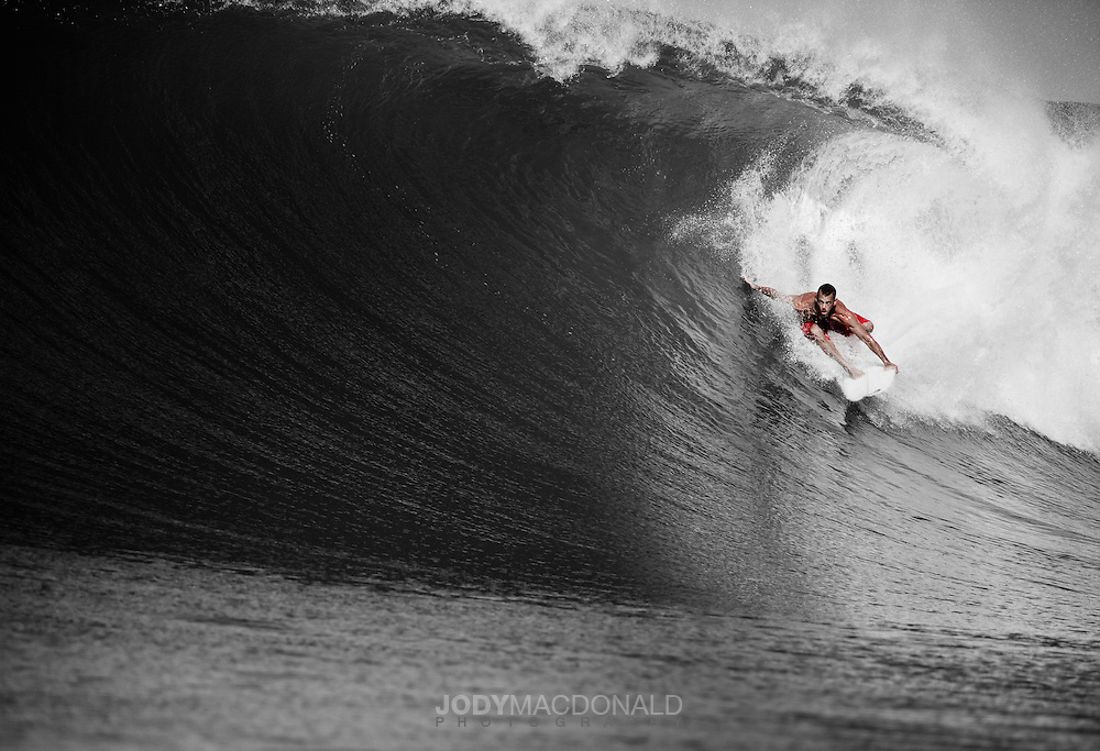 Surfer Lono Humphries tucks into a massive barreling right-hand unknown wave in Sumba, Indonesia