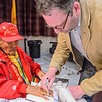 010414       Cable Hoover<br /> <br /> Filmmaker David DeJonge, left, traces the hand of codetalker Chester Nez into a copy of Nez's during a meet and greet at the WWI film festival at El Morro Theater Saturday.