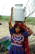 A Muslim Maldhari girl carries water to her nomad camp...by Michael Benanav - mbenanav@gmail.com