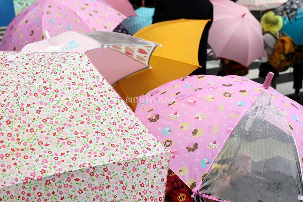 little school children walking with bright colored umbrellas
