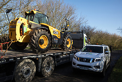 Denham, UK. 11 February, 2020. Environmental activists from Extinction Rebellion, Stop HS2 and Save the Colne Valley 'slow walk' in front of a large truck transporting a JCB forklift truck to a HS2 site at Denham in the Colne Valley. A HS2 contractors' vehicle passes on the other side of the road. Contractors working on behalf of HS2 are rerouting electricity pylons through a Site of Metropolitan Importance for Nature Conservation (SMI) in conjunction with the high-speed rail link.