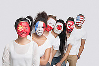 Portrait of Multi-ethnic group of friends with various national flags painted on their faces standing in queue against white background