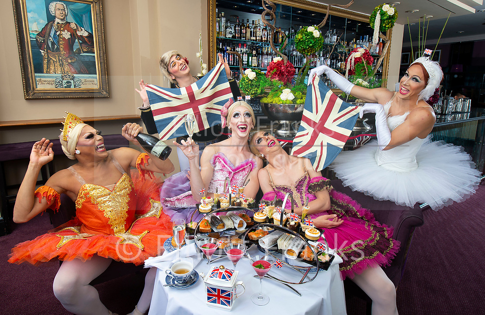 Hailing from New York City, the all-male comedy ballet company Les Ballets Trockadero de Monte Carlo, affectionately know as The Trocks, have arrived in London for the start of their Dance Consortium presented UK and Ireland 2018 Tour opening at The Peacock theatre<br /> Press photocall 10th September 2018 <br /> <br /> 'More tea? The New York based all-male comedy ballet company Les Ballets Trockadero de Monte Carlo, aka The Trocks, enjoy afternoon tea at The Strand Palace Hotel Gin Palace Bar ahead of their Dance Consortium presented UK and Ireland Tour 2018 kicking off at London's The Peacock theatre' <br /> <br /> Raffaele Morra (Company Ballet Master plus male dancer 'waiter' for 'afternoon tea' part of photoshoot) <br /> <br /> Dancers as ballerinas: <br /> <br /> Robert Carter (OLGA SUPPHOZOVA)<br /> <br /> Carlos Hopuy (ALLA SNIZOVA)<br /> <br /> Joshua Thake (EUGENIA REPELSKII)<br /> <br /> Alberto Pretto (NINA IMMOBILASHVILI)<br /> <br /> Photograph by Elliott Franks
