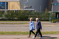 © Licensed to London News Pictures. 26/03/2020. WATFORD, UK.  A couple walks by the Making of Harry Potter Experience at Warner Bros. Studios in Leavesden, Hertfordshire, just outside London, home to the Harry Potter, Fantastic Beasts and recent Mission Impossible movies.  Work on productions has all but ceased due to the coronavirus pandemic.  Workers in the industry comprise mainly the self-employed (from cameramen to background artistes) and later today Rishi Sunak, Chancellor of the Exchequer, is due to launch a financial support plan for them and members of the self employed in other industries.  Photo credit: Stephen Chung/LNP