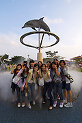 Okinawa Churaumi Aquarium at Ocean Expo Park. Girls having fun doing a group souvenir photo with dolphin sculpture and artificial fog.