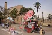 A tourist stall with Coca-Cola umbrella in Luxor Square, with the Mosque of Abu el-Haggag's minaret, far left, Luxor Temple, Nile Valley, Egypt.