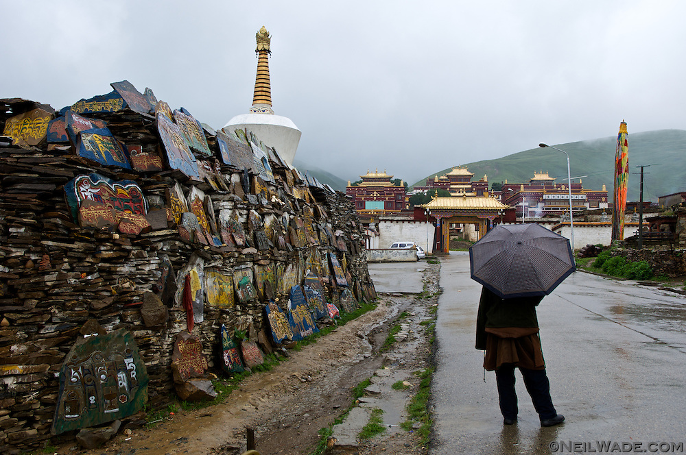 A man stands in the rain next to a big mani stone pile in front of the Litang Cho?de Monastery in Litang, Tibet.  Mani stones are prayers carved into rocks then piled up near important religious places.