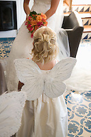 Girl wearing butterfly wings at wedding ceremony