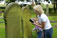 lady looking at details on a gravestone with her daughters