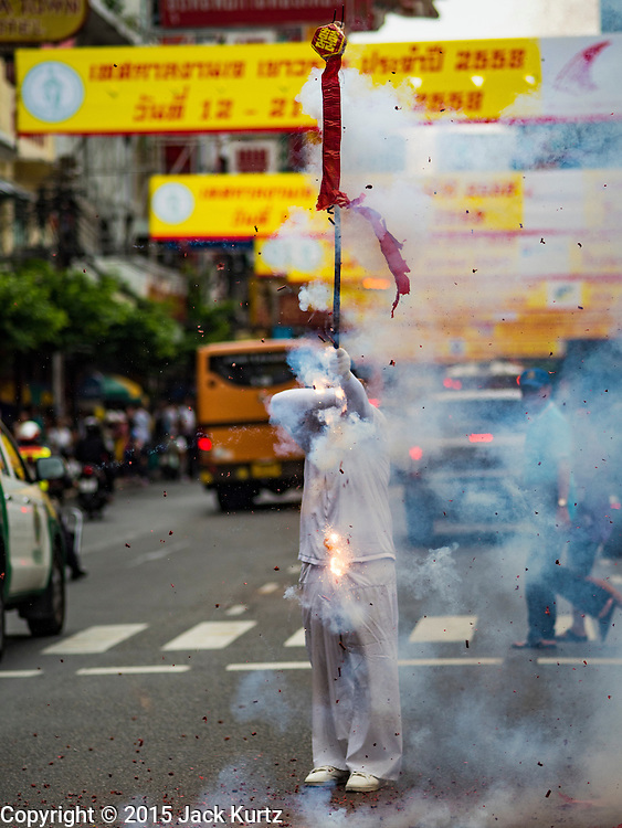 12 OCTOBER 2015 - BANGKOK, THAILAND:  Firecrackers are set off on Yaowarat Road on the first day of the Vegetarian Festival in Bangkok's Chinatown. The Vegetarian Festival is celebrated throughout Thailand. It is the Thai version of the The Nine Emperor Gods Festival, a nine-day Taoist celebration beginning on the eve of 9th lunar month of the Chinese calendar. During a period of nine days, those who are participating in the festival dress all in white and abstain from eating meat, poultry, seafood, and dairy products. Vendors and proprietors of restaurants indicate that vegetarian food is for sale by putting a yellow flag out with Thai characters for meatless written on it in red.     PHOTO BY JACK KURTZ