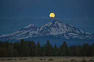 """A """"super moon"""" sets over North and Middle Sister peaks near Sisters, Oregon."""