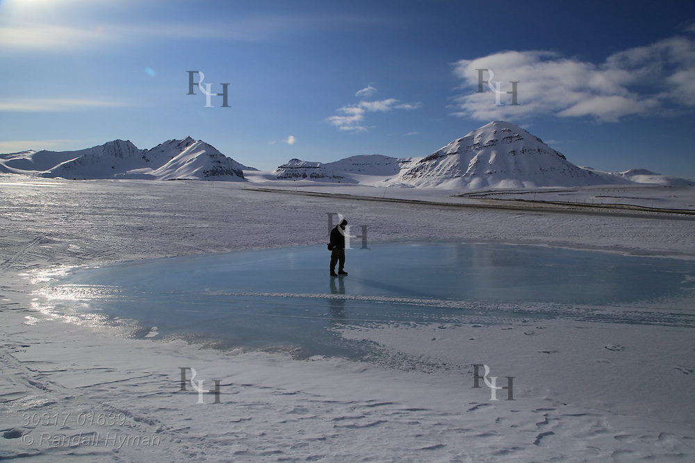 Man stands on frozen meltwater pond in April at the international science village of Ny-Alesund on Spitsbergen island in Kongsfjorden; Svalbard, Norway.