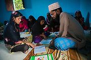 Next to the local Imam, Tabasum Khatun, 14, is studying the Holy Koran in the Madrassa of Algunda village, pop. 1000, Giridih District, rural Jharkhand, India.