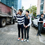 Middle school boys waiting for friends after school in Busan, South Korea.