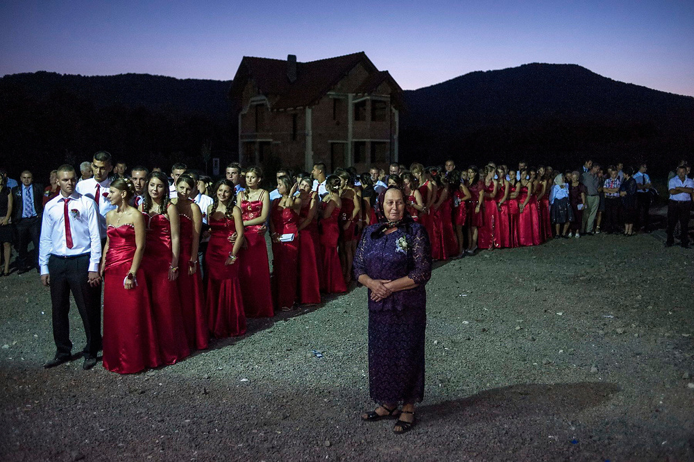 30 brides maids, all wearing dresses made from the same red material, line up to take their place at Maricuta and Ionut's wedding. Maricuta and Ionut both live in Paris. He works in the construction industry and she is a housekeeper. They have come back to their native village to get married.