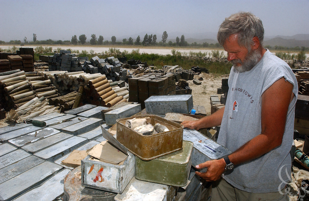 U.S. special forces Master Sgt. Scott sorts through various al-Qaeda weapons July 3, 2002 at the Khost airbase in southeastern Afghanistan. U.S. special forces in the region uncovered the weapons as part of a 30 ton cache last week after receiving tips of al-Qaeda activity in the area.