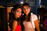 Two young women are standing backstage before performing at one of the regular night dance shows being set up during the yearly Sonepur Mela, Asia's largest cattle market, in Bihar, India.
