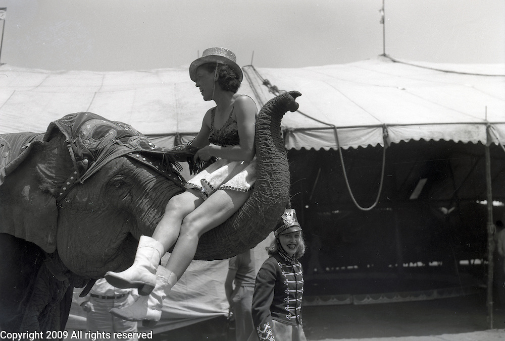 Kelly Miller Brothers Circus' performer Mrs. Williams gets lifted by an elephant in a documentary photo. North Platte, Nebraska. 1945