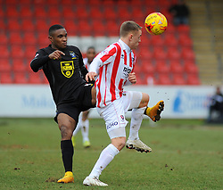 Bury's Kelvin Etuhu and Cheltenham Town's Eliot Richards jostle for possession  - Photo mandatory by-line: Nizaam Jones - Mobile: 07966 386802 - 14/02/2015 - SPORT - Football - Cheltenham - Whaddon Road - Cheltenham Town v Bury - Sky Bet League Two