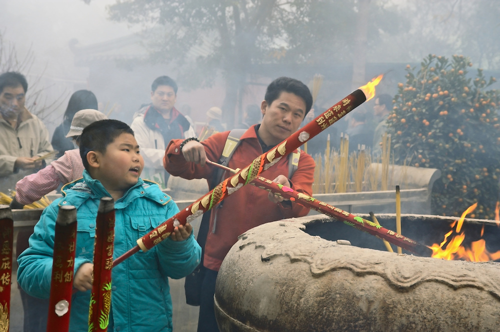 Man and boy light large incense sticks at Po Lin monastery on foggy first day of Lunar New Year 2009, Lantau, Hong Kong
