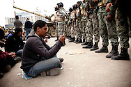 An anti-government protester prays in front of the Egyptian army in Tahrir Square in Cairo, Egypt, on Saturday, Feb. 5, 2011.